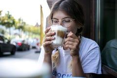 De leuke vrij jonge vrouw drinkt het schuim van de koffiemelk royalty-vrije stock foto