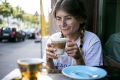 De leuke vrij jonge vrouw drinkt het schuim van de koffiemelk stock fotografie