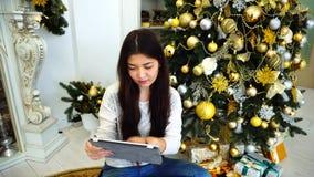 De leuke Vrouw die Tablet voor online het Boeken of Reserve van Vakantie gebruiken schrijft en zit op Achtergrondkerstboom toe stock footage