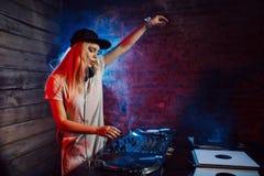 De leuke vrouw die van DJ pret speelmuziek hebben bij clubpartij stock afbeelding