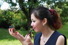De leuke vrouw kijkt in spiegel schildert ook lippen. Stock Foto