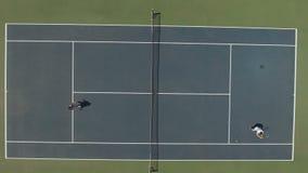 De leuke vrouw in kleding en de jonge kerel in borrels spelen tennis bij het hof stock footage