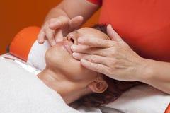 De leuke vrouw krijgt professionele gezichtsmassage, lymfatische drainage stock fotografie