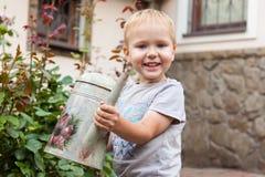 De leuke wateren van de babyjongen de bloemen op de achteryard, moedermedewerker royalty-vrije stock afbeeldingen