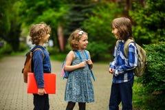 De leuke weinig schoolstudenten spreken levendig op het schoolplein stock afbeeldingen
