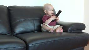 De leuke zitting van de babyjongen op zwarte bank met afstandsbediening thuis stock videobeelden
