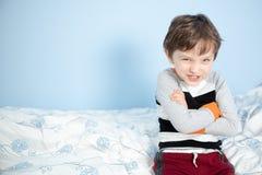 De leuke zitting van de 6 éénjarigenjongen op de rand van het bed Royalty-vrije Stock Foto
