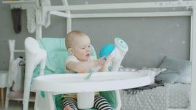 De leuke zitting van het babymeisje op highchair die plaat likken stock footage