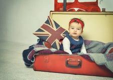 De leuke zitting van het Babymeisje in oude uitstekende koffer Stock Afbeeldingen