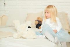 De leuke zitting van het peutermeisje op het bed met haar zacht speelgoed in een lichte ruimte Gelukkig verjaardagsconcept Stock Foto's