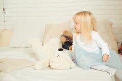 De leuke zitting van het peutermeisje op het bed met haar zacht speelgoed in een lichte ruimte Gelukkig verjaardagsconcept Royalty-vrije Stock Fotografie