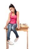 De leuke zitting van het tienermeisje op haar bureau Stock Foto's