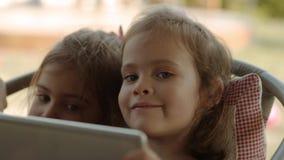 De leuke zusters houden een tablet en letten op een beeldverhaal op het stock video