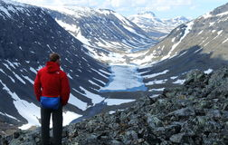 De leurder in helder gekleurd openluchttoestel bewondert de mening over de Kungsleden-wandelingssleep in Zweden Stock Afbeeldingen