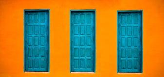 De levendige heldere oranje voorgevel van het muurhuis met drie blauwgroene gesloten deuren op de grote lege oranje brede achterg stock fotografie