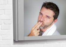 De levensstijl isoleerde portret van de jonge aantrekkelijke en gelukkige mens die aan zich badkamersspiegel bekijken met handdoe royalty-vrije stock foto's