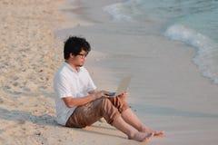 De levensstijl ontspande de jonge Aziatische mens met laptop zitting op het strand De vakantieconcept van de zomer stock foto