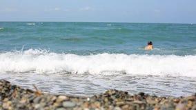 De levensstijlmens loopt in het overzees op een kiezelsteenstrand en zwemt op de golf stock video