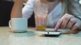 De levensstijlvrouw van de koffiestad op telefoon het drinken bericht van de koffie het texting tekst op smartphoneapp zitting bi Stock Afbeelding