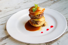 De lever van het kalf met appelen Gelegde lagen met saus op een witte plaat Royalty-vrije Stock Foto