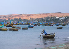 De levering van mensenrijen aan de vissersvloot van kust wordt verankerd die Royalty-vrije Stock Foto's