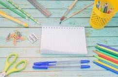 De levering van de school Blauwe ballpens, kleurentellers, potloden in een gele tribune, twee leeswijzers, heerser, gele ruber, k stock foto