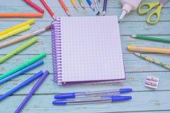 De levering van de school Kleurenpotloden, notaboek, blauwe pennen, sciccors, tellers, lijm, scherper, klemmen Royalty-vrije Stock Afbeeldingen
