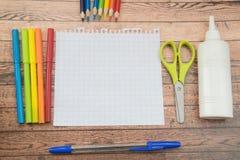 De levering van de school Kleurenpotloden, notaboek, blauwe pennen, sciccors, tellers, lijm, scherper, klemmen Royalty-vrije Stock Foto's