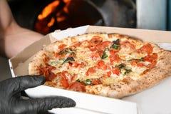 De de leveringsdoos van de chef-kokholding met traditionele oven bakte Italiaanse pizza in keukenrestaurant royalty-vrije stock fotografie