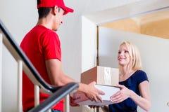 De leveringsmens in rode eenvormig levert kartondozen aan deur stock afbeelding