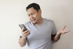 De Lezing die van jonge Mensentexting bij Zijn Telefoon het Droevige Schreeuwen babbelen royalty-vrije stock afbeelding