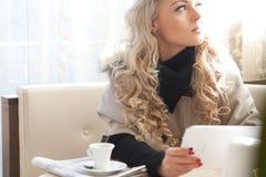 De lezing van de blondevrouw op een tablet stock fotografie