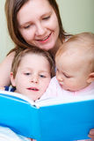 De lezing van de familie in bed royalty-vrije stock foto's