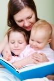 De lezing van de familie in bed stock foto