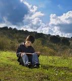 De lezing van de jongen openlucht royalty-vrije stock fotografie