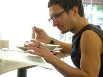 De lezing van de mens & het hebben van ontbijt Stock Fotografie