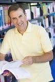 De lezing van de mens in bibliotheek Stock Foto