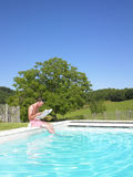 De Lezing van de mens bij Rand van Zwembad Stock Fotografie