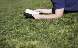 De lezing van de mens op gras royalty-vrije stock foto's