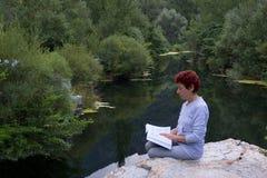 De lezing van de vrouw op het meer. Stock Foto