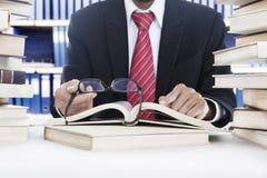 De lezing van de zakenman zonder glazen in de bibliotheek Royalty-vrije Stock Foto's