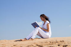 De lezing van het meisje op strand Stock Fotografie
