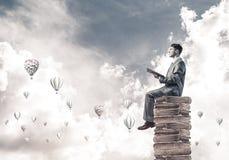 De lezingsboek en aerostaten die van de mensenstudent rond in lucht vliegen Stock Afbeeldingen