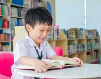 De lezingsboek van de jongensstudent in bibliotheek stock foto's