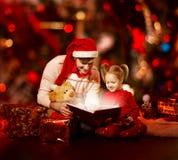 De lezingsboek van de Kerstmisfamilie. Vader en kind die magisch FA openen Stock Afbeeldingen