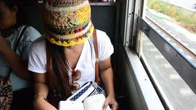 De lezingsboek van de reizigersvrouw op Spoorwegtrein in Ayutthaya Thailand stock video