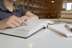 De lezingsboek van de vrouw in bibliotheek Royalty-vrije Stock Foto's