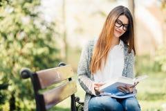 De lezingsboek van de vrouw op parkbank Stock Afbeelding