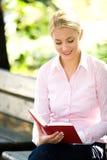 De lezingsboek van de vrouw in openlucht royalty-vrije stock foto's