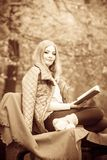 De lezingsboek van het blondemeisje in de herfstlandschap stock afbeeldingen